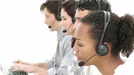 képviselő : Competitive businesspeople working in a call center against a white background
