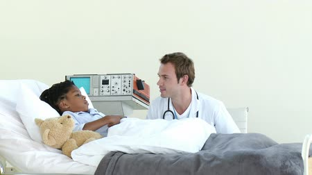 incelenmesi : Positive doctor talking with a little boy in hospital
