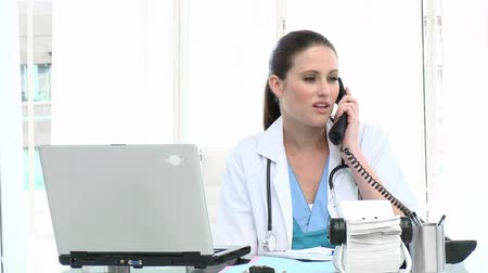 titkár : Attractive female doctor on phone in a hospital Stock mozgókép
