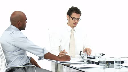 испанец : Two young businessmen having a meeting against a white background Стоковые видеозаписи