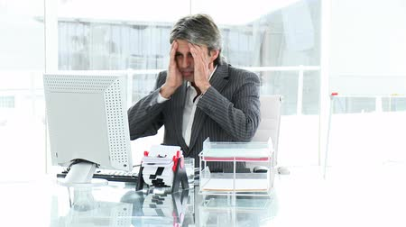 aflição : Upset executive working at a computer in the office Stock Footage