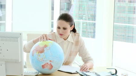 globalização : Elegant businesswoman looking at a terrestrial globe in the office