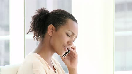 afro americana : Smiling businesswoman talking on phone in the office
