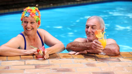 romantic couple : Happy mature couple relaxing in the swimming pool with cocktails