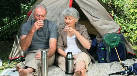 поход : Seniors drinking coffee sitting near a tent in the Park