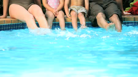 ayaklar : Family sitting at the poolside with feets in water