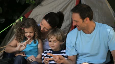 gerekçesiyle : Family palying in front of a tent in a Park Stok Video