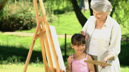 внучка : Young girl painting a canvas with her grandmother in the Park