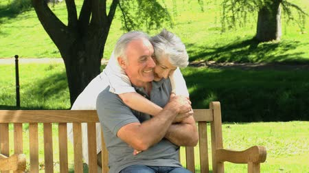 idősek : Woman hugging her husband sitting on a bench in the Park