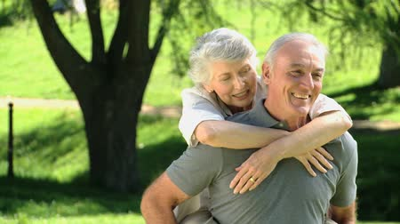 idősek : Senior man carrying his aged wife in the Park