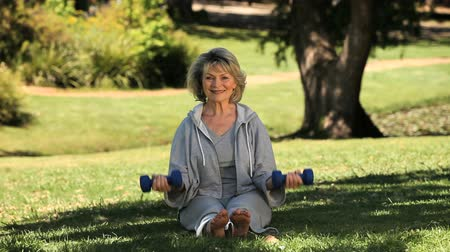 aeróbica : Senior woman working her muscles with dumbbells on the grass in the Park Vídeos