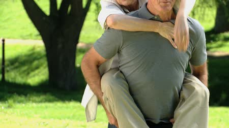 romantic couple : Elderly man carrying his aged wife in the Park