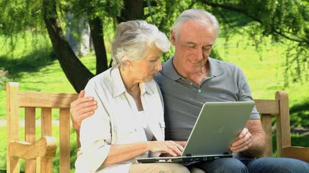 senior lifestyle : Elderly cute couple looking at a computer sitting on a bench in the Park