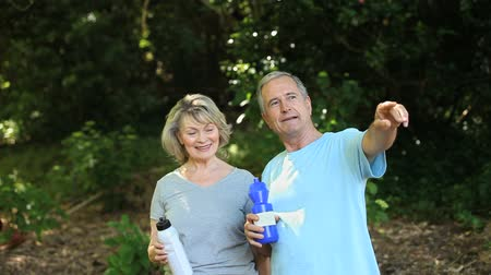jogging : Elderly couple taking a break after drinking in a Forest Stock Footage