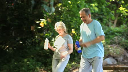 drink cans : Elderly couple drinking after exercice in the Forest