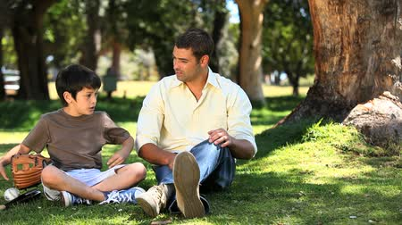 etkinlik : Father talking with his son sitting on the grass near a tree in the Park Stok Video