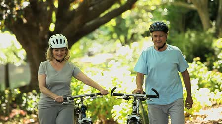 idősek : Senior couple walking and pushing bikes in the Forest