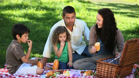 пикник : Happy family feasting at a picnic in the Park