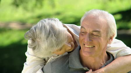 romantic : Close up of a old woman hugging her husband sitting on a bench in the Park Stock Footage