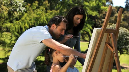 malarstwo : Parents and children painting a canvas in the Park