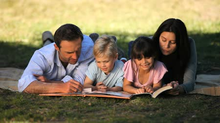 ler : Family reading a book lying on a tablecloth in the Park Vídeos