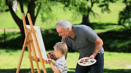 grandchild : Young noy painting a white canvas with grandad in the Park Stock Footage