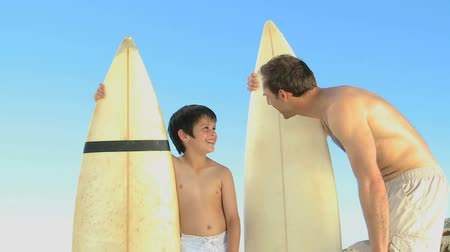 surf : Father and son with surfboard talking with each other on the beach Dostupné videozáznamy