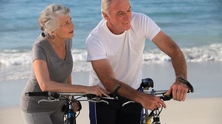 senior lifestyle : Elderly couple doing flexibility exercices sitting on the beach