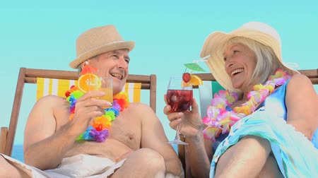 amadurecer : Mature couple toasting with cocktails sitting on beach chairs against a blue sky background