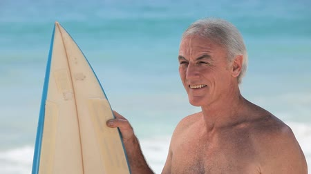 surf : Aged man looking at the ocean with a surfboard on the beach Dostupné videozáznamy