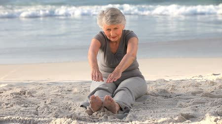 гибкость : Elderly woman doing flexibility exercice sitting on the beach Стоковые видеозаписи