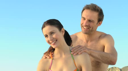 masaż : Man massaging his wife on the beach against a blue sky background