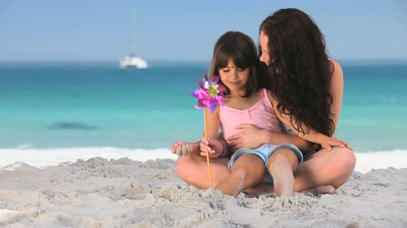 купаться : Mother and daughter playing with a toy sitting on the beach Стоковые видеозаписи