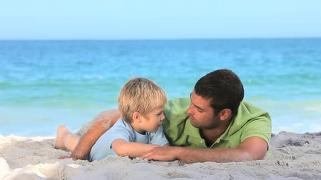 купаться : Father enjoying time with his son lying on the beach