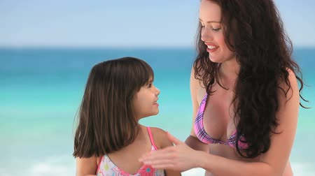 colocando : Beautiful mother putting sunscreen on her daughter sitting on the beach
