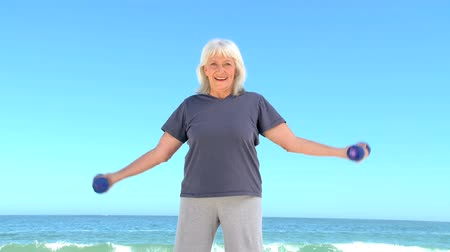 aeróbica : Senior woman working his muscles with dumbbells on the beach