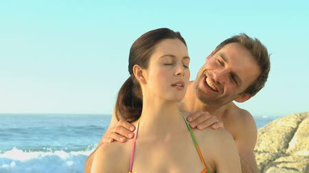 masaż : Handsome man massaging his wife on the beach