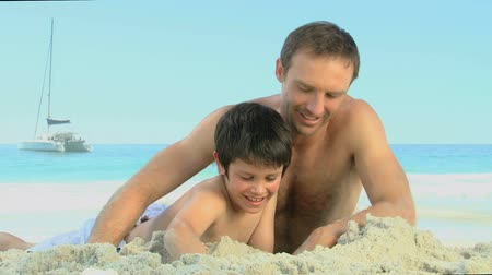otec : Father helping his son to build a sand castle on the beach