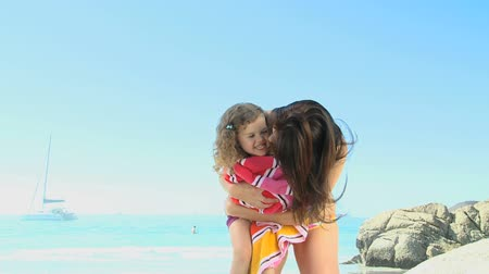 объятие : Attractive mother hugging his daughter with a beach towel near the ocean