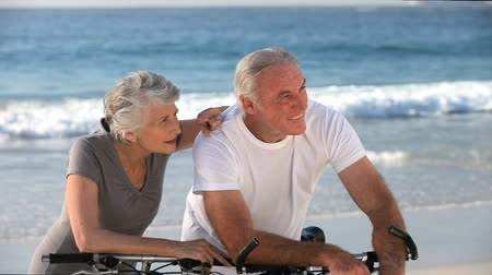 two people talking : Aged couple with bikes looking at the beach near the ocean Stock Footage
