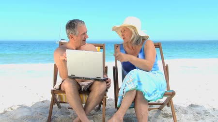 amadurecer : Elderly man showing to his wife a video on the laptop on the beach Stock Footage