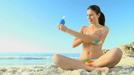 colocando : Beautiful woman putting sunscreen on herself sitting on the beach