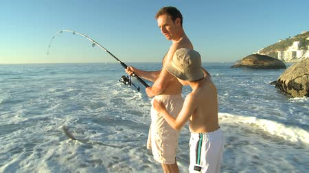 otec : Attractive man fishing with his son on the beach