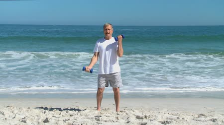 fit : Mature man working his muscles with dumbbells on the beach