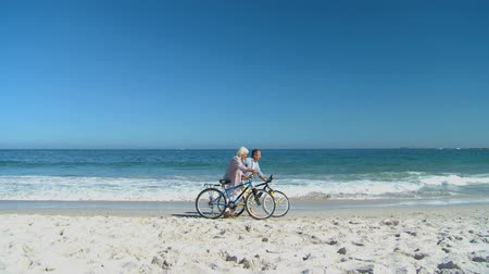 two people talking : Aged woman talking with his husband during a walk with bikes on the beach Stock Footage
