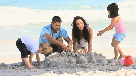 zamek : Parents building a sand castle with their children on the beach