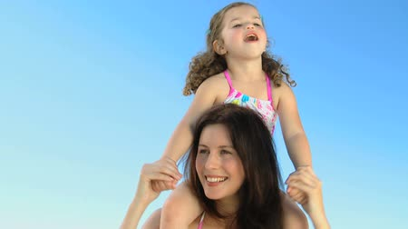 transportar : Happy mother carrying her daughter on her shoulders against a blue sky background Stock Footage