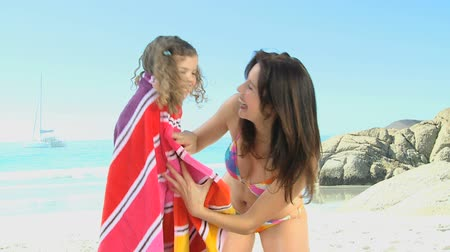 объятие : Mother hugging her daughter with a towel on the beach