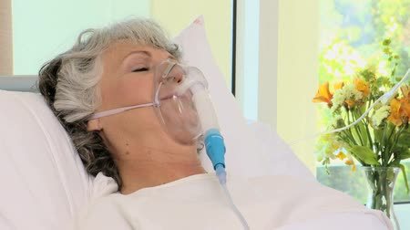 oksijen : Woman lying on the bed with an oxygen mask in a hospital room