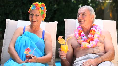 repousante : Old man and woman relaxing on a deckchair near the pool